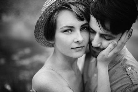 stylish hipster couple hugging at lake. man and woman embracing, in love relaxing in summer park, picnic date. girl in fashionable modern dress and straw hat . black white photo