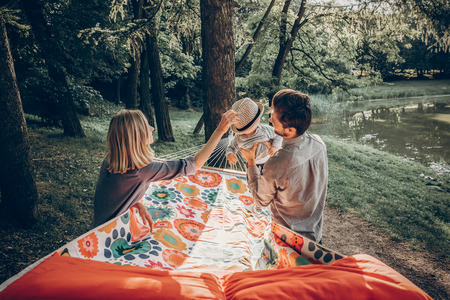 Junge Familie, die mit Sohn auf einer Hängematte im Park auf Campingausflug, Hippie-Mutter setzt einen Weinlesehut auf einem Jungen nahe dem hübschen Vater, der ihn hält, Familienurlaub spielt Lizenzfreie Bilder - 85658953