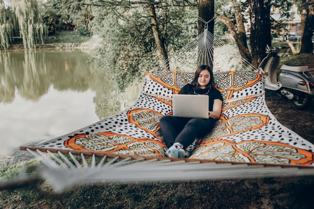 Beautiful brunette woman relaxing on hammock outdoors near lake in the forest, freelancer working in the park while resting in hammock, freelance concept Archivio Fotografico