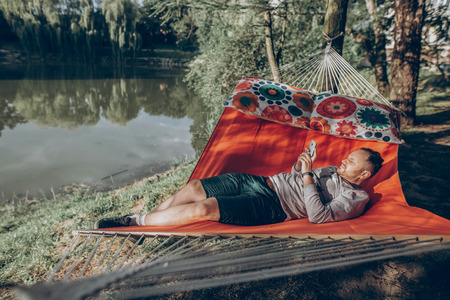 Handsome man relaxing on a hammock on a camping trip, stylish hipster man lying on a hammock thinking and looking at phone near a lake, relaxation concept Archivio Fotografico