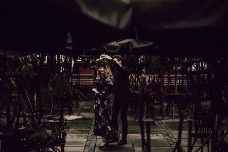 stijlvolle zigeuner paar verliefd dansen in avond stadsstraat op café terras. vrouw en man zacht knuffelen, romantische Franse atmosferische moment. gepassioneerde liefdesstemming.