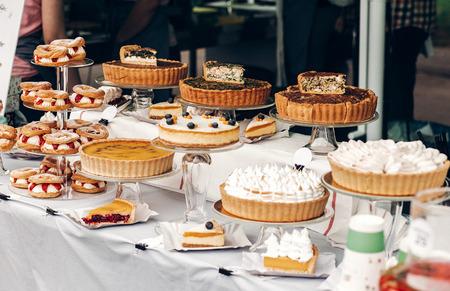 heerlijke taarten en taart met slagroom op tafel op straatvoedsel festival. candybar met lekkere snoepjes, catering op de bruiloft receptie. open keuken buiten. zomerpicknick
