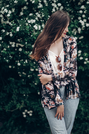 Hippie-Frau mit der Sonnenbrille, die auf Hintergrund des blühenden Busches mit weißen Blumen von spirea aufwirft. sinnliches Porträt boho Mädchens in der windigen Stadtstraße. Platz für Text. Frühling Sommerzeit Lizenzfreie Bilder