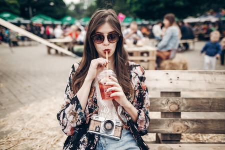 Stilvolle Hipster Frau trinkt Limonade. Coole Boho Mädchen in Denim und böhmische Kleidung, halten Cocktail sitzen auf Holzbank am Straßenfutter Festival. Sommer. Sommerferien reisen Lizenzfreie Bilder