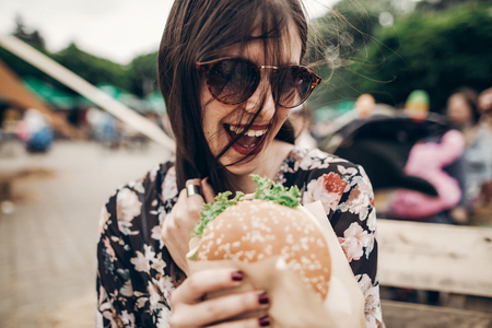 stylish hipster woman holding juicy burger and eating at street food festival.summer vacation travel. Archivio Fotografico