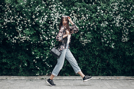 happy hipster woman with sunglasses having fun at blooming bush with white flowers of spirea. boho girl jumping and smiling in modern clothes, emotional moment. space for text Archivio Fotografico