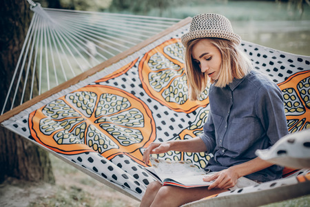 stylish hipster woman reading book and relaxing in hammock in sunny summer park. blonde girl resting in forest, smiling and enjoying day. summer vacation, space for text