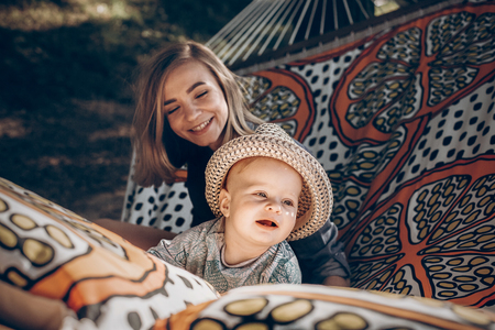 happy hipster mother playing with her cute little son on hammock in summer sunny park. stylish mom with kid relaxing in forest and cuddling having fun. space for text
