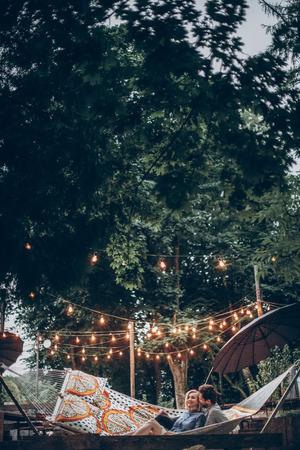 stijlvolle hipster paar knuffelen en ontspannen in hangmat onder retro verlichting in avond zomer park. man knuffelen vrouw en rust in het bos. ruimte voor tekst. rustieke liefde concept