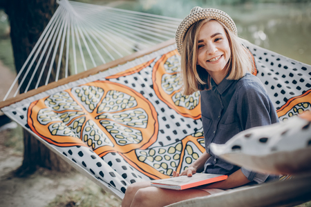 stylish hipster woman reading book and relaxing in hammock in sunny summer park. blonde girl resting in forest, smiling and enjoying day. student studies at campus, space for text