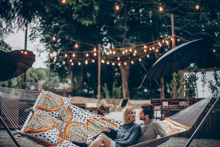 stylish hipster couple cuddling and relaxing in hammock under retro lights in evening summer park. man hugging woman and resting in forest. space for text. rustic love concept