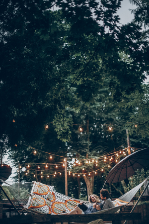 stylish hipster couple cuddling and relaxing in hammock under retro lights in evening summer park. rustic man and woman embracing and resting in forest. space for text. summer vacation 版權商用圖片 - 85459141