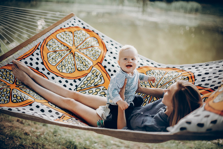 young hipster mother playing with her cute little son on hammock in summer sunny park. stylish happy mom with kid relaxing in forest and smiling, having fun. space for text. family vacation