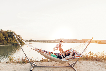 happy stylish family playing with cute daughter, relaxing in hammock on summer vacation in evening sun light on the beach. hipster couple with child resting and having fun in sunset. space for text Archivio Fotografico