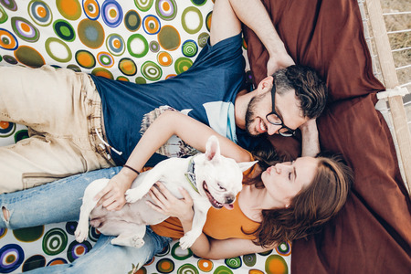 happy hipster couple with bulldog relaxing in hammock on the beach in sunset light, summer vacation. stylish family with dog cuddling and resting, cute moments. space for text