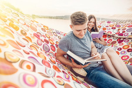 happy hipster couple reading books and relaxing in hammock in sunset light on the beach, summer vacation. stylish hipsters holding books and resting in summer evening. space for text
