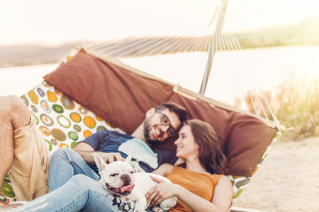 happy hipster couple with bulldog relaxing in hammock on the beach in sunset light, summer vacation. stylish family with dog cuddling and resting, romantic moments. space for text Archivio Fotografico