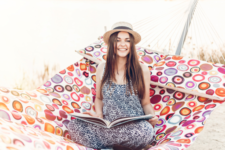 beautiful hipster girl with big book relaxing in hammock on the beach in summer evening light. happy woman in straw hat resting and reading in sun, summer holiday. space for text
