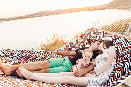 happy stylish family playing with cute daughter and cuddling, relaxing in hammock on summer vacation in evening sun light on the beach. hipster couple kissing and resting in sunset. space for text