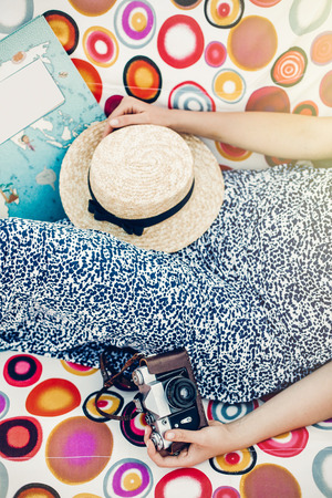 boho hipster girl with retro camera, book and straw hat relaxing in hammock on summer vacation in sun light. top view. woman resting in sun rays. space for text. travel and wanderlust