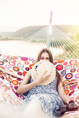 beautiful hipster girl relaxing in hammock on the beach in summer evening light. happy woman in straw hat resting and enjoying moment in sun, summer vacation. space for text Archivio Fotografico