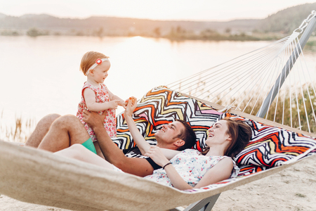 happy stylish family with cute daughter relaxing in hammock on summer vacation in evening sun light on the beach. hipster couple with child resting and having fun in sunset