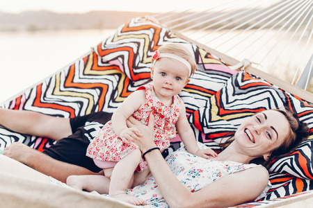 happy stylish family playing with cute daughter, relaxing in hammock on summer vacation in evening sun light on the beach. hipster couple with child resting in sunset. space for text. summer holiday