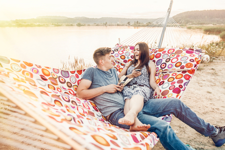 happy couple looking at phones and smiling, relaxing in hammock in sunset light on the beach. stylish hipsters having fun, and resting on summer vacation. social media concept, space for text