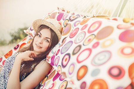 beautiful hipster girl relaxing in hammock on the beach in summer evening light. happy woman in straw hat resting in sun rays, summer holiday. space for text. peaceful moment Stockfoto