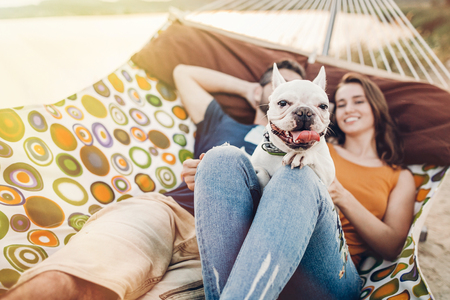 happy hipster couple with bulldog relaxing in hammock on the beach in sunset light, summer vacation. stylish family with funny dog resting, cute moments. space for text
