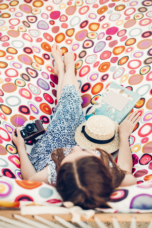 boho hipster girl holding retro camera and straw hat while relaxing in hammock on summer vacation in sun light. top view. woman resting in sun rays, summer holiday travel. space for text Stockfoto