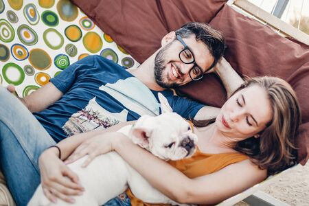 happy hipster couple with bulldog relaxing in hammock on the beach in sunset light, summer vacation. stylish family with dog cuddling and having fun, cute moments in summer evening Stockfoto