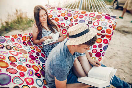 happy hipster couple reading books and relaxing in hammock in sunset light on the beach, summer vacation. stylish hipsters resting and studying together on summer vacation.  space for text