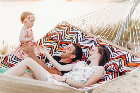happy stylish family relaxing in hammock on summer vacation in evening sun light on the beach. hipster couple with child resting and having fun in sunset. summer  holiday, space for text