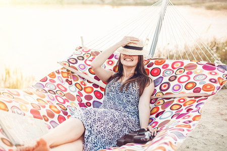 happy beautiful hipster girl relaxing in hammock on the beach in summer evening light. joyful boho woman in straw hat resting and having fun in sun, summer vacation. space for text