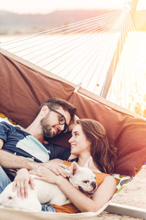 happy hipster couple with bulldog relaxing in hammock on the beach in sunset light, summer vacation. stylish family with dog cuddling and resting, romantic moments. space for text Stockfoto
