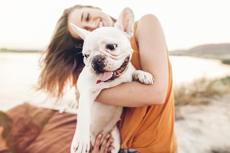 夕日の光、夏の休暇でビーチにブルドッグと遊んで幸せな流行に敏感な女性。面白い犬休んで、ハグと太陽の下で楽しんでスタイリッシュな女の子