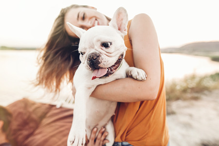 happy hipster woman playing with bulldog on the beach in sunset light, summer vacation. stylish girl with funny dog resting, hugging and having fun in sun, cute moments. space for text Stockfoto