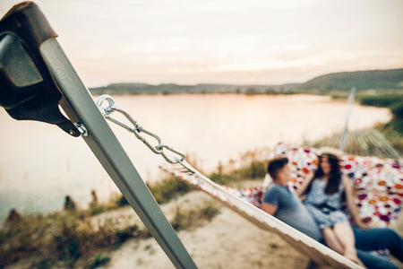travel hammock. happy hipster couple relaxing in hammock in sunset light on the beach, summer vacation. summer holidays. steel detail. space for text.