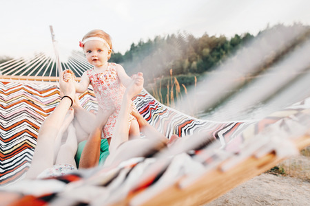 happy stylish family playing with cute daughter, relaxing in hammock on summer vacation in evening sun light on the beach. hipster couple with child resting and having fun in sunset. space for text Stockfoto
