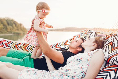 Strong young father holding his baby daughter in hands with happy hipster mother, smiling family relaxing in a hammock on a beach near lake at sunset, family vacation concept
