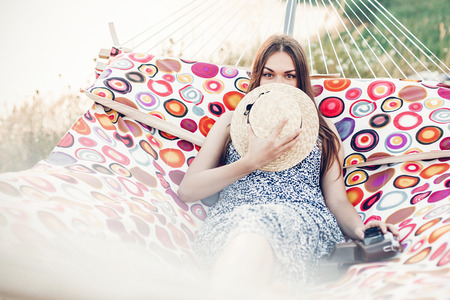 Beautiful hipster girl in stylish dress hiding behind hat and smiling while resting on a hammock on the beach, freelancer woman with her film camera lying on hammock Zdjęcie Seryjne