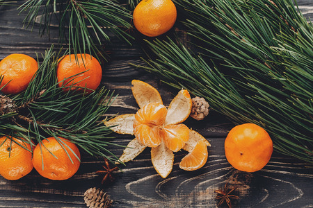 christmas image flat lay. christmas peeled tangerine and mandarins and anise pine cones on rustic wooden background top view. xmas seasonal greetings. space for text. winter holidays