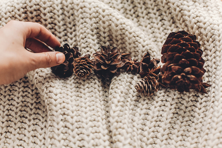 decorating: hand holding pine cone on background of cozy sweater with anise on rustic background, space for text. xmas seasonal greetings card. winter holidays mood. christmas decor preparation