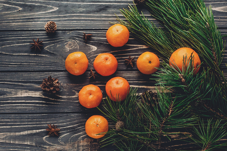 christmas image flat lay. green fir branches with tangerine on rustic wooden background top view. eco design. xmas seasonal greetings. space for text. winter holidays Stock Photo
