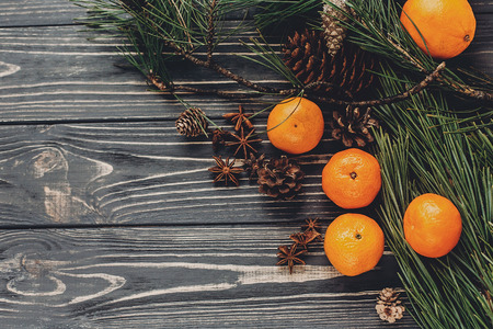 christmas image flat lay. green fir branches with tangerine and anise and pine cones on rustic wooden background top view. eco design. xmas seasonal greetings. space for text. winter holidays