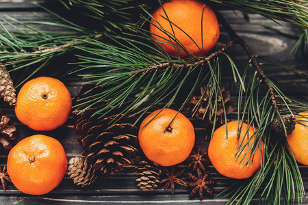 green fir branches with tangerine and anise and pine cones on rustic wooden background top view. christmas simple image.  xmas seasonal greetings. space for text. winter holidays Stock Photo
