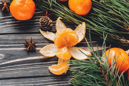 christmas peeled tangerine and mandarins and anise pine cones on rustic wooden background. xmas seasonal greetings. space for text. winter holidays. holiday mood Stock Photo