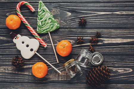 christmas striped candy and tree and snowman lollipops  with tangerine and anise pine cones on rustic wooden background top view. xmas seasonal greetings. space for text. winter holidays