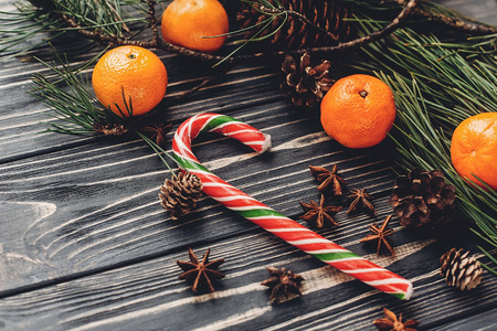 christmas striped candy and fir branches with tangerine and anise  on rustic wooden background. xmas seasonal greetings. space for text. winter holidays